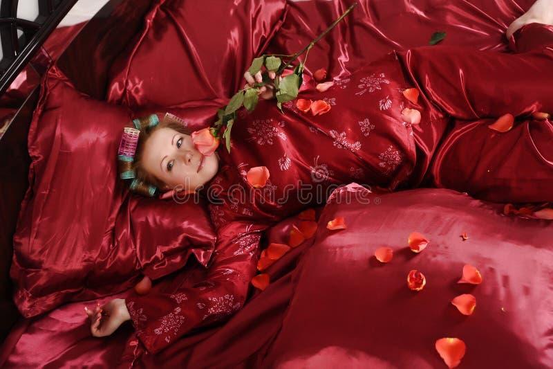 Mujer en los pijamas rojos que mienten en una cama en el lino rojo de seda con bigud?es de pelo y una rosa en su mano foto de archivo