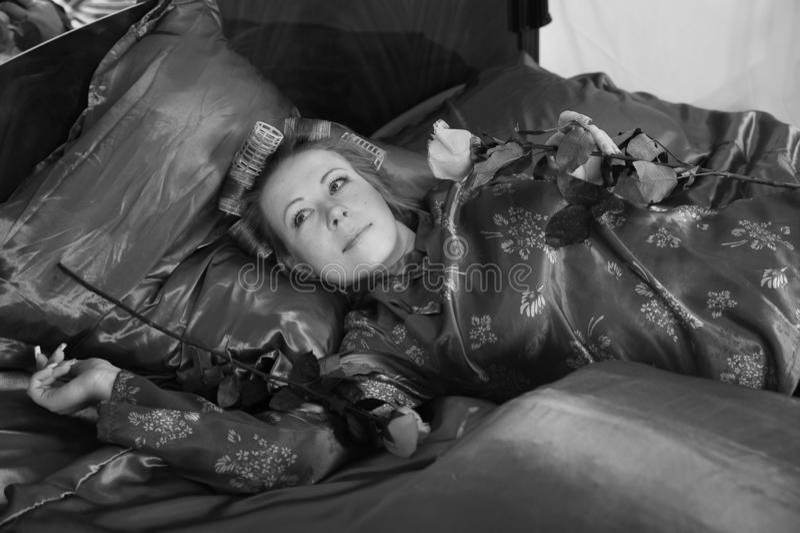 Mujer en los pijamas rojos que mienten en una cama en el lino rojo de seda con bigud?es de pelo y una rosa en su mano imágenes de archivo libres de regalías