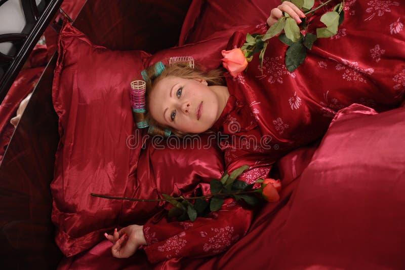Mujer en los pijamas rojos que mienten en una cama en el lino rojo de seda con bigud?es de pelo y una rosa en su mano fotografía de archivo
