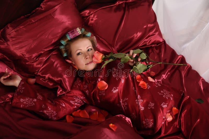 Mujer en los pijamas rojos que mienten en una cama en el lino rojo de seda con bigud?es de pelo y una rosa en su mano foto de archivo libre de regalías