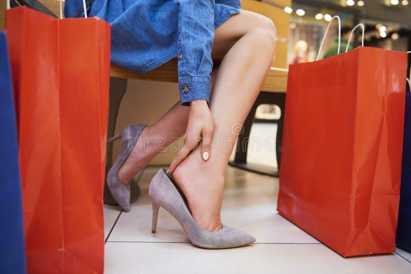 Mujer en los zapatos de los tacones altos que sienten el dolor en los tobillos imágenes de archivo libres de regalías