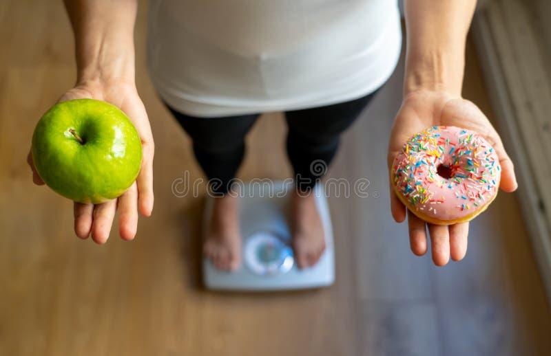 Mujer en manzana de medición de la tenencia del peso de la escala y anillos de espuma que eligen entre la comida sana o malsana imagen de archivo