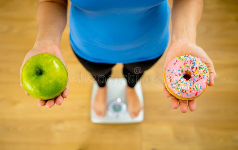 Mujer en manzana de medici?n de la tenencia del peso de la escala y anillos de espuma que eligen entre la comida sana o malsana fotografía de archivo libre de regalías