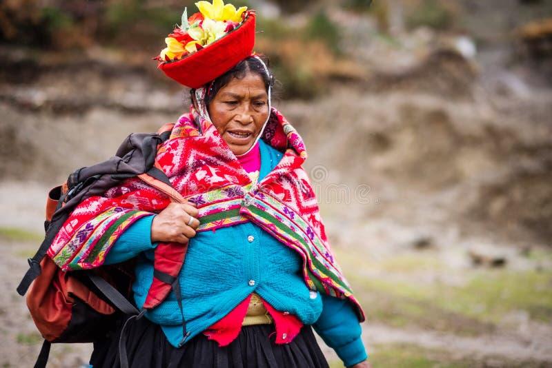 Mujer en mochila roja nacional de la tenencia de la ropa y del sombrero en Cusco imágenes de archivo libres de regalías