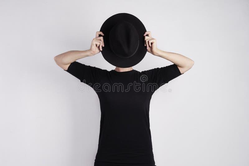 Mujer en negro ocultada su cara por el sombrero negro Concepto de metáfora, de drama, de emoción de la piel o de personalidad fotografía de archivo libre de regalías