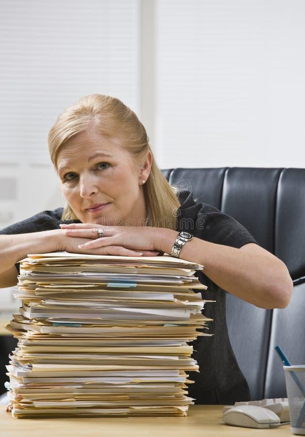 Mujer en oficina con papeleo foto de archivo