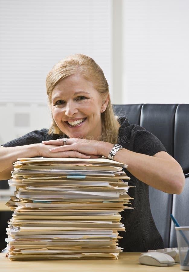 Mujer en oficina con papeleo fotos de archivo libres de regalías