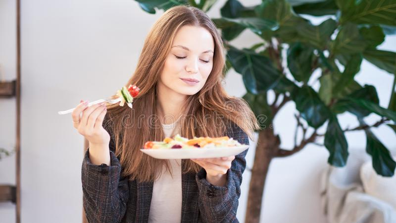 Mujer en oficina que come la ensalada en el lugar de trabajo Concepto de almuerzo en el trabajo y la consumici?n de la comida san fotografía de archivo libre de regalías