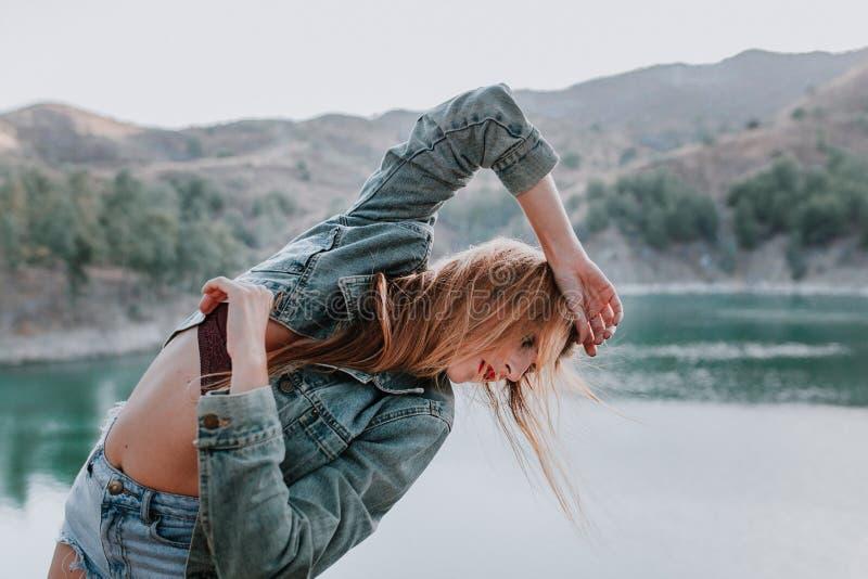 Mujer en pantalones cortos y chaqueta que presenta en naturaleza con un lago en el fondo imagen de archivo