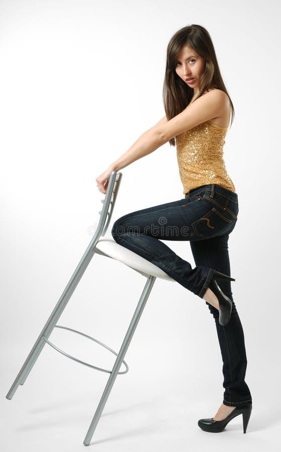 Mujer en pantalones vaqueros con el taburete, vista lateral imagen de archivo