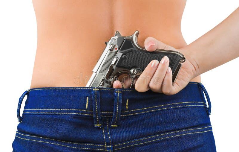 Mujer en pantalones vaqueros y arma foto de archivo