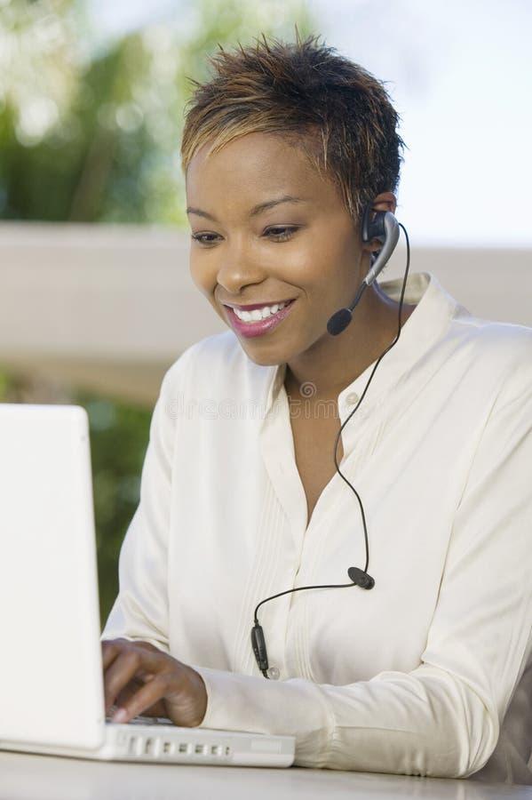 Mujer en patio usando el ordenador portátil y las auriculares imagenes de archivo