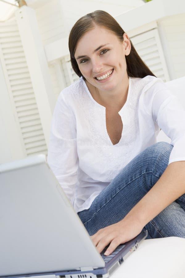 Mujer en patio usando la computadora portátil fotos de archivo libres de regalías