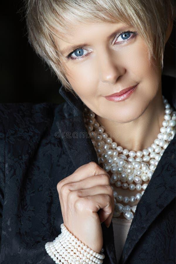 Mujer en perlas en su 40s imagenes de archivo