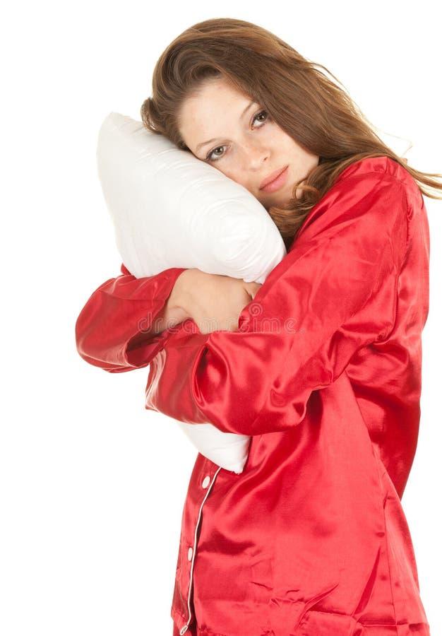 Mujer en pijamas rojos con la almohadilla blanca imagenes de archivo