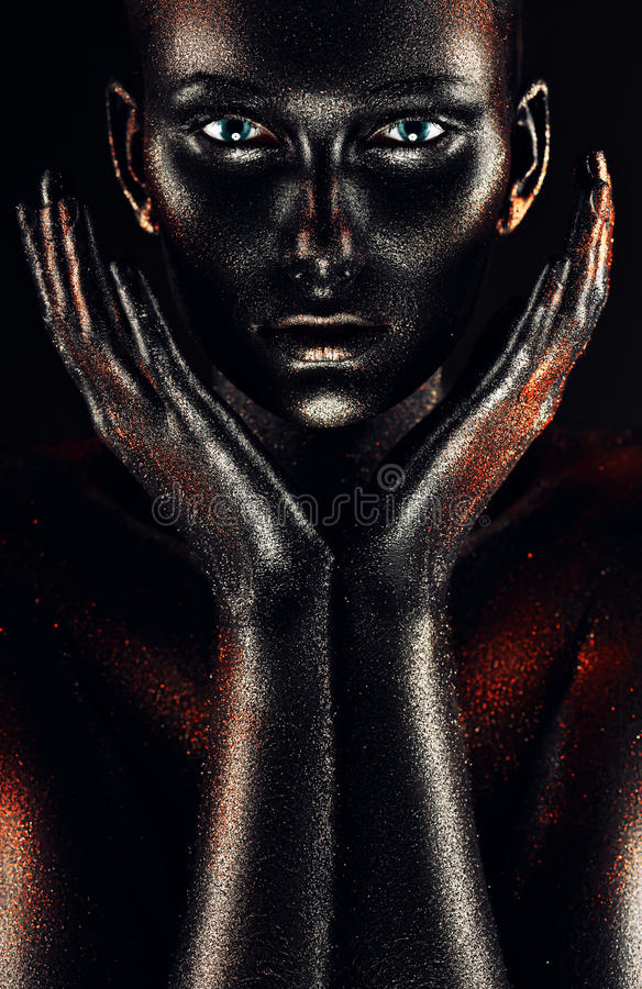 Mujer en pintura negra con las manos alrededor de mejillas imagen de archivo