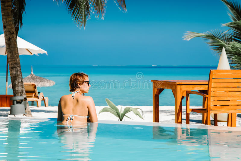 Mujer en piscina en la isla tropical imagen de archivo