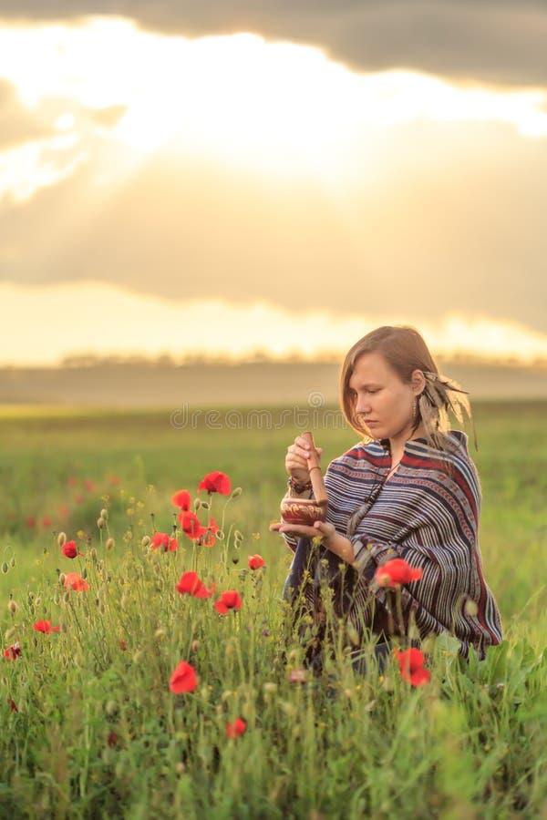 Mujer en poncho con el cuenco del canto en campo de flor fotografía de archivo libre de regalías