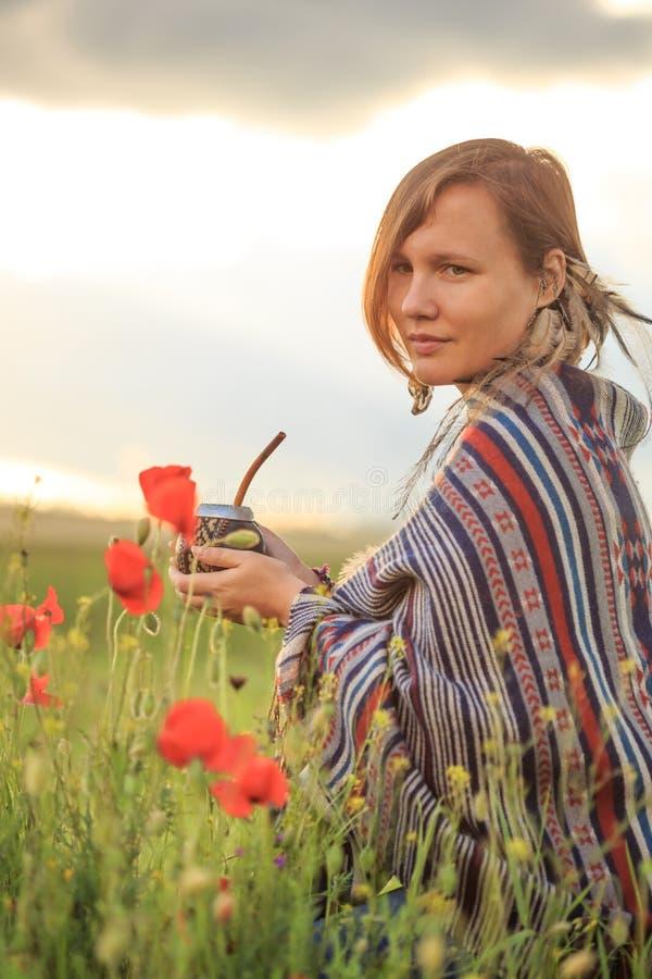 Mujer en poncho con la calabaza en campo de flor foto de archivo libre de regalías