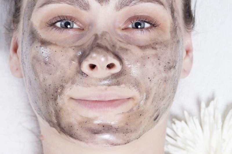 Mujer en primer del balneario Cara de la chica joven con la máscara facial negra en tratamientos del balneario Cuidado de piel Sk imagenes de archivo