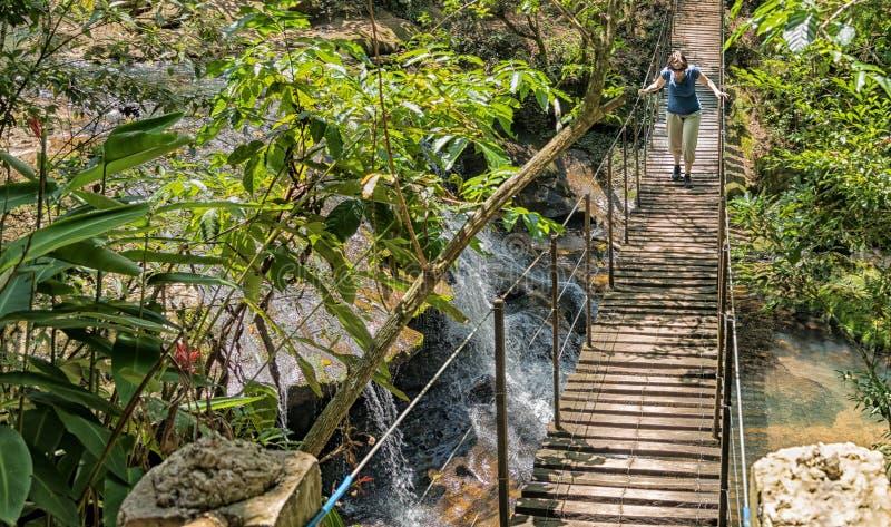 Mujer en puente colgante sobre una cascada en la selva tropical de Paraguay fotografía de archivo libre de regalías