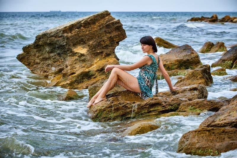 Mujer en roca en playa foto de archivo