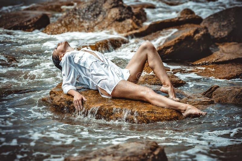 Mujer en roca en playa fotos de archivo libres de regalías