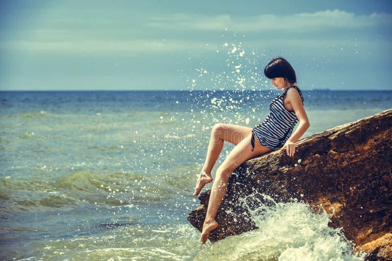 Mujer en roca en playa fotografía de archivo
