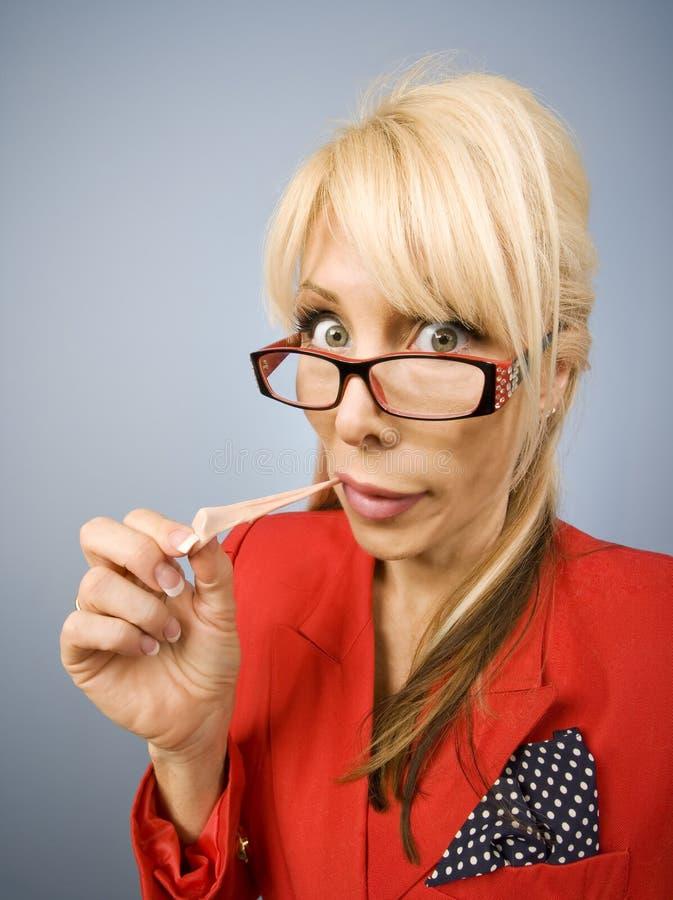 Mujer en rojo con la goma que hace una cara divertida imágenes de archivo libres de regalías
