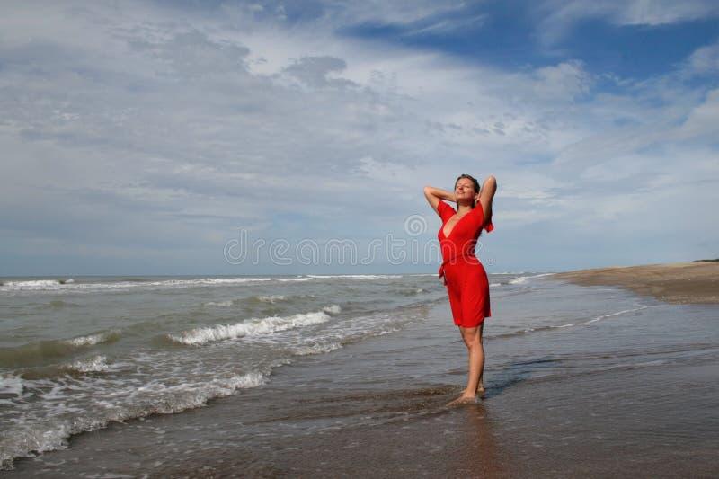 Mujer en rojo en costa oceánica bajo el cielo azul imagenes de archivo