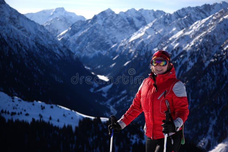 Mujer en rojo en cuesta del esquí imagenes de archivo