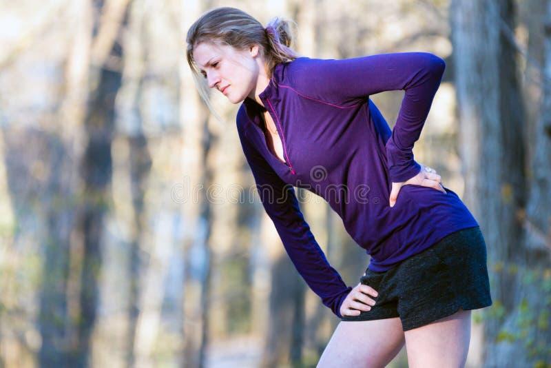 Mujer en ropa de la aptitud en sendero que experimenta dolor de espalda fotografía de archivo