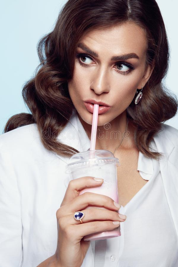 Mujer en ropa de la moda y maquillaje con la bebida a disposición fotografía de archivo