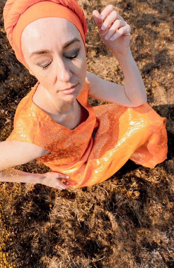 Mujer en ropa del este Se asperja con las lentejuelas del oro Portret emocional imagen de archivo libre de regalías