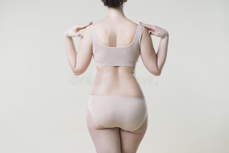 Mujer en ropa interior beige en el fondo del estudio, celulitis en cuerpo femenino fotos de archivo libres de regalías