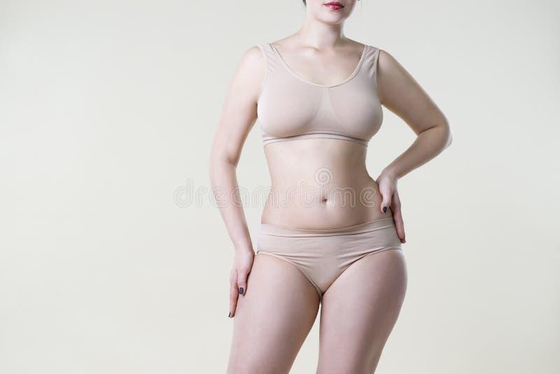 Mujer en ropa interior beige en el fondo del estudio, celulitis en cuerpo femenino imagenes de archivo