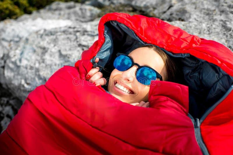 Mujer en saco de dormir en la montaña imagen de archivo