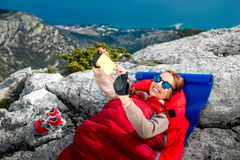Mujer en saco de dormir en la montaña imágenes de archivo libres de regalías