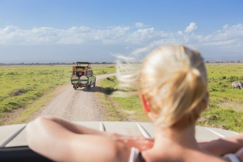Mujer en safari africano de la fauna observando la naturaleza del jeep abierto del safari del tejado imágenes de archivo libres de regalías