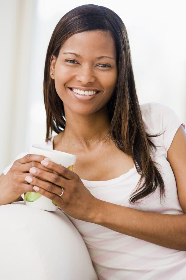 Mujer en sala de estar con la sonrisa del café fotografía de archivo