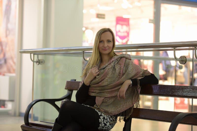 Mujer en sentarse de los abrigos del beige fotos de archivo libres de regalías