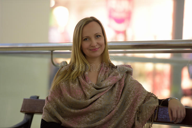 Mujer en sentarse de los abrigos del beige foto de archivo