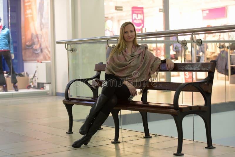 Mujer en sentarse de los abrigos del beige foto de archivo libre de regalías