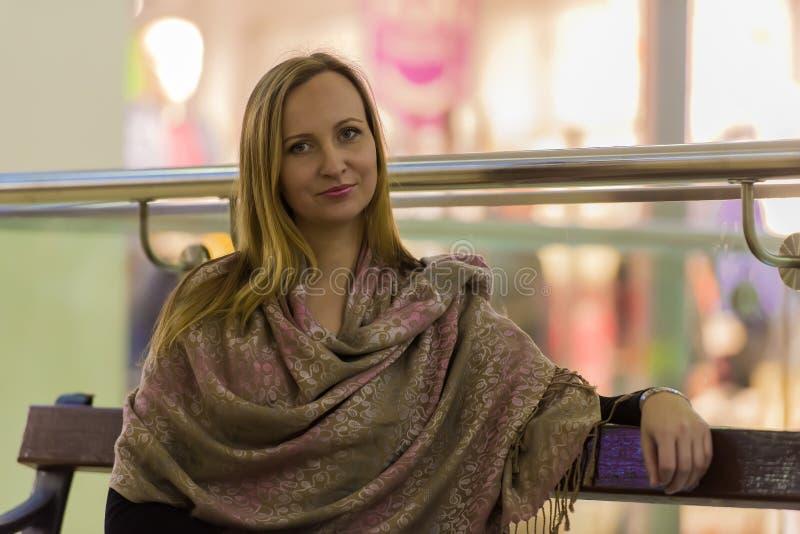 Mujer en sentarse de los abrigos del beige imágenes de archivo libres de regalías