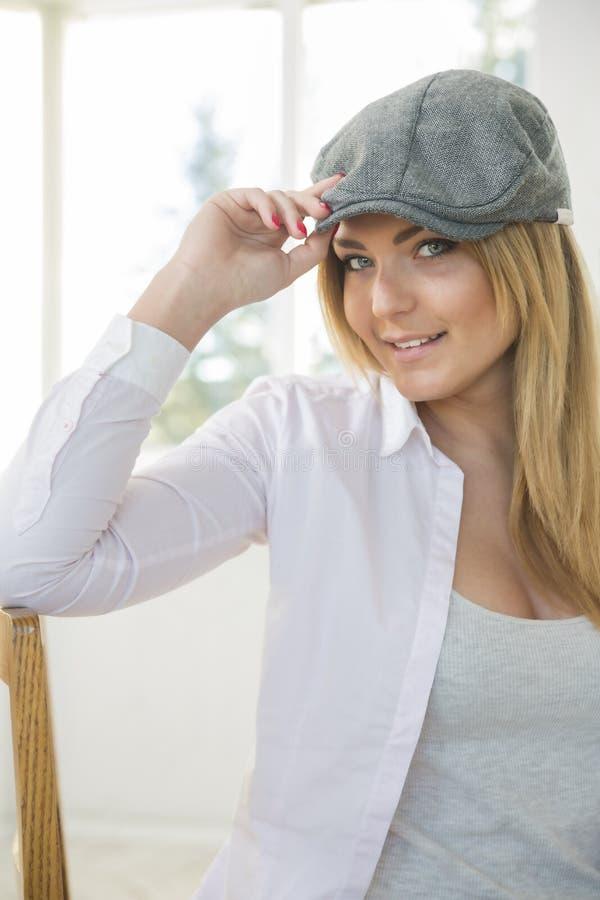 Mujer en silla con el sombrero gris elegante imagen de archivo libre de regalías