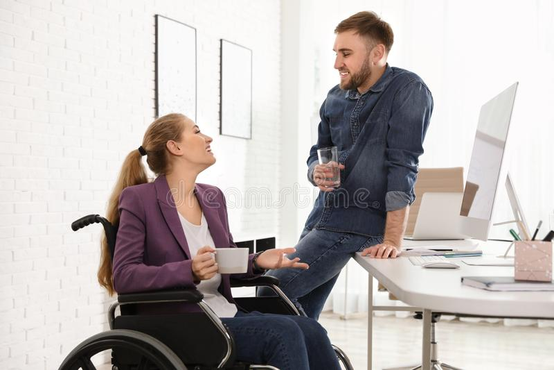 Mujer en silla de ruedas con su colega imágenes de archivo libres de regalías