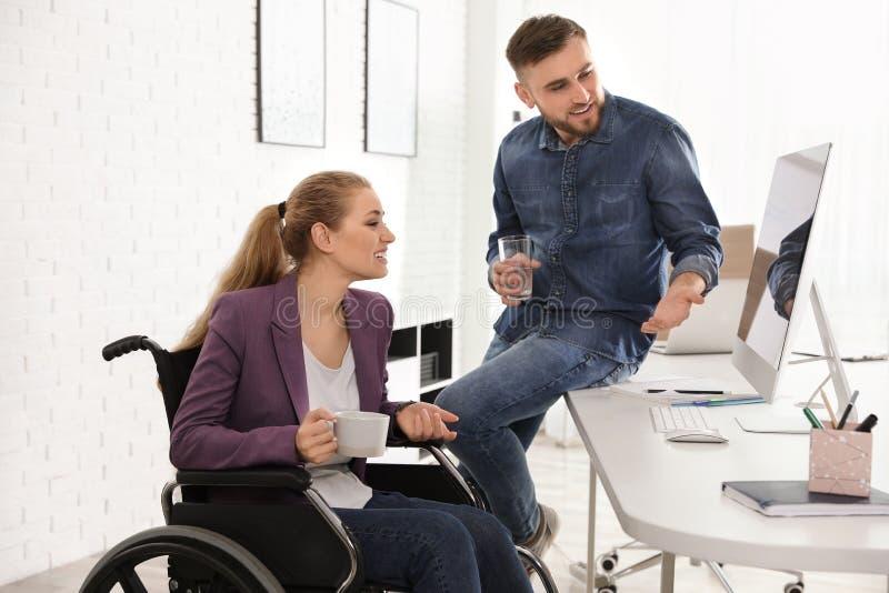Mujer en silla de ruedas con su colega foto de archivo