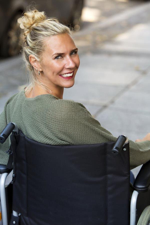 Mujer en silla de ruedas que sonríe en la cámara foto de archivo