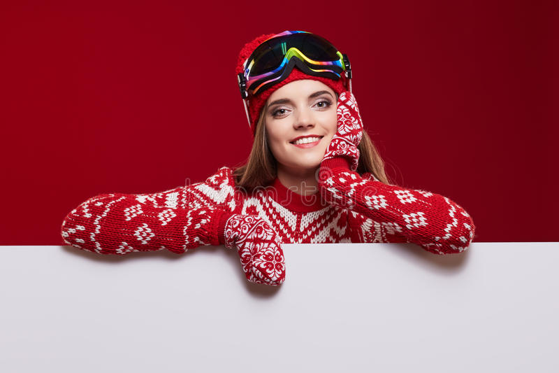 Mujer en sombrero colorido y guantes que miran furtivamente de detrás whiteboard fotografía de archivo libre de regalías