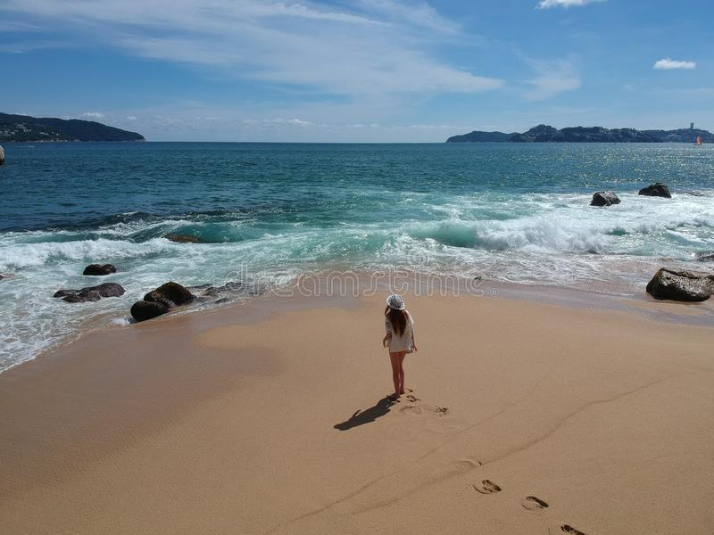 Mujer en sombrero en la playa tropical Acapulco, México imagenes de archivo